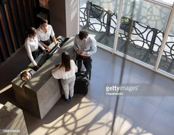 Schwarz-Manager und Recepcionist Check-in ein paar und Mann sein Smartphone betrachten