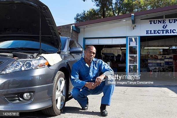 Black mechanic squatting near car