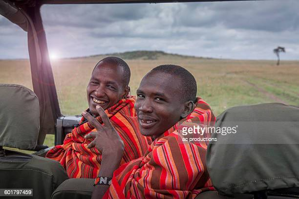 Black men smiling in car in remote field