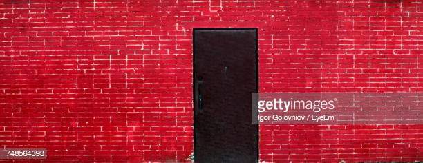 black metallic door amidst red brick wall - igor golovniov stock pictures, royalty-free photos & images