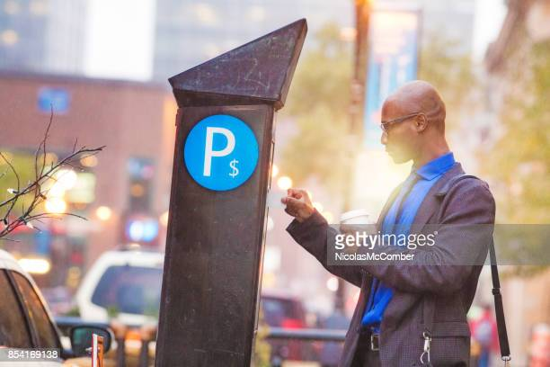 black mid adult businessman paying his parking in rainstorm - parking meter stock photos and pictures