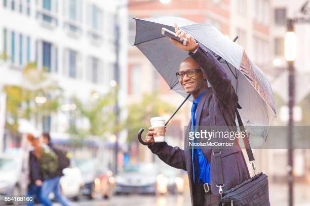 Black mid adult businessman signaling his rideshare in rainstorm