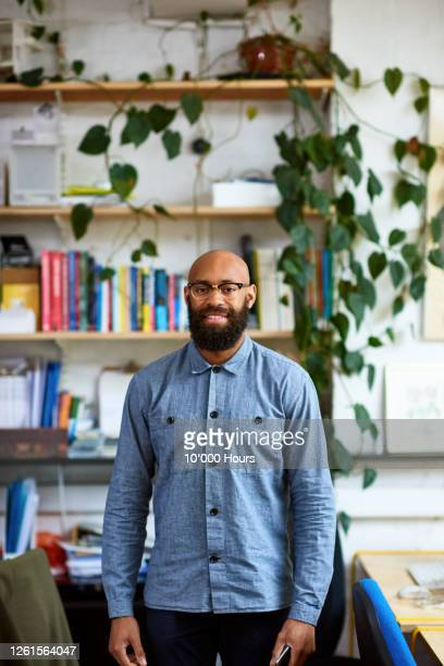 black mid adult entrepreneur in office smiling at camera - waist up stock pictures, royalty-free photos & images