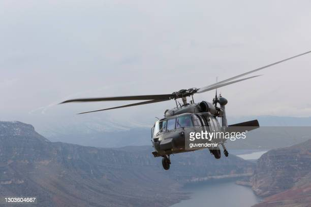 black military helicopter in flight - helicopter stock pictures, royalty-free photos & images