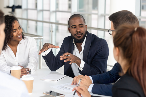 Black millennial boss leading corporate team during briefing in boardroom 1139630453