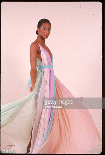 Black model Beverly Johnson shown full length modeling Halston long dress made of pastel vertical pieces of flowing material, probably chiffon which...
