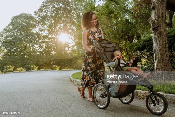 black mom pushing a baby stroller outdoors during summer - baby stroller stock pictures, royalty-free photos & images