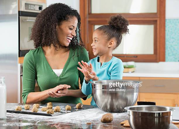 Black mother and daughter baking in kitchen
