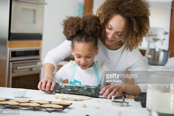 Black mother and daughter baking together