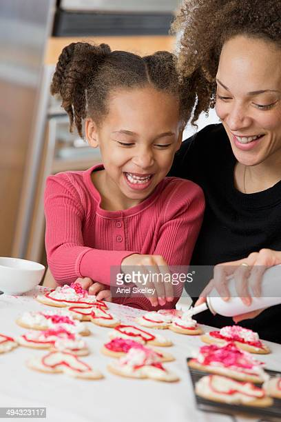 Black mother and daughter decorating cookies