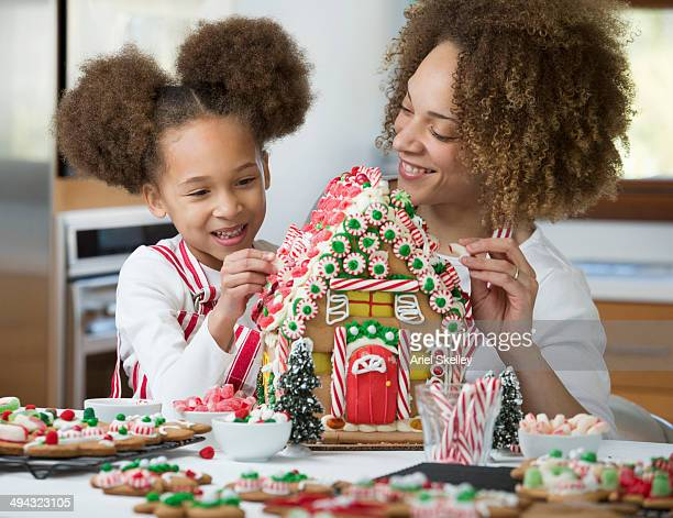 Black mother and daughter decorating gingerbread house