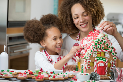 Black mother and daughter decorating gingerbread house - gettyimageskorea