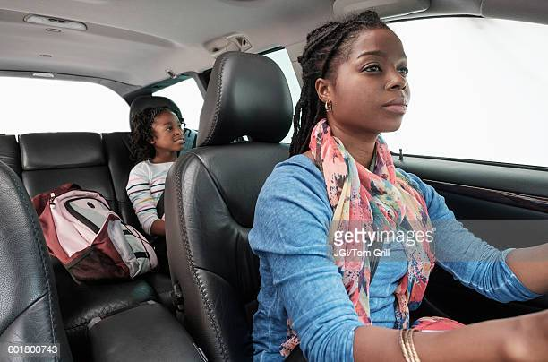 Black mother and daughter driving in car