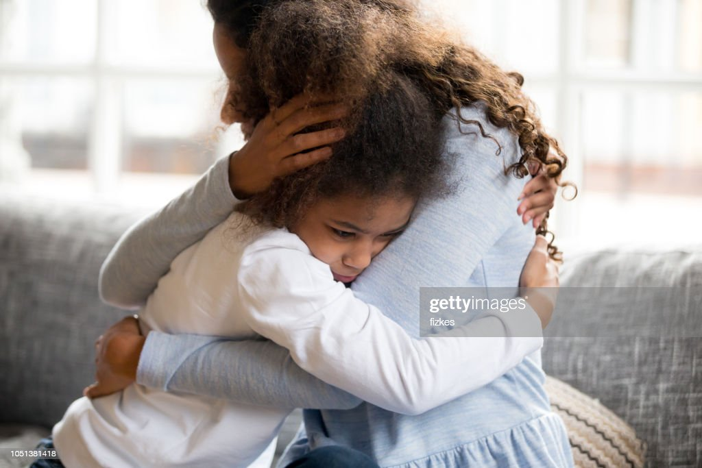 Black mother and daughter embracing sitting on couch : Stock Photo