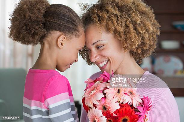 black mother and daughter holding bouquet of flowers - happy mothers day mom stock-fotos und bilder