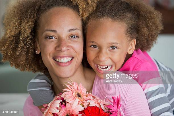 black mother and daughter holding bouquet of flowers - black mothers day stock pictures, royalty-free photos & images