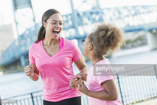 Black mother and daughter holding hands,  laughing