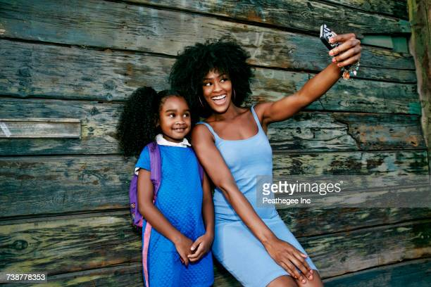 Black mother and daughter posing for cell phone selfie
