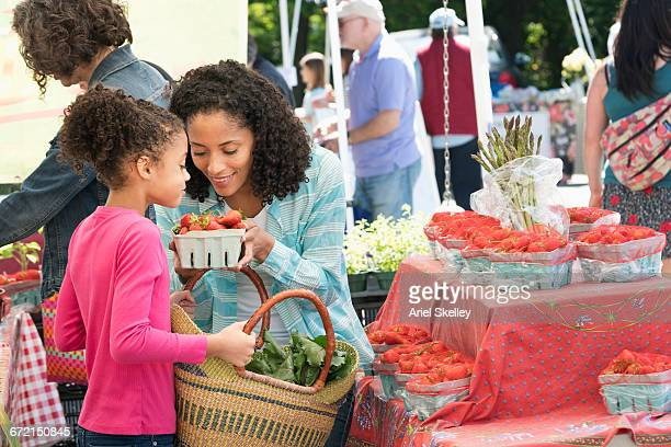 Black mother and daughter smelling strawberries at farmers market