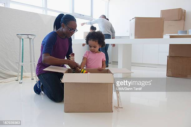 Black mother and daughter unpacking in new home