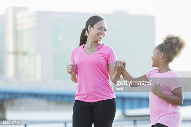 Black mother and daughter walking, holding hands, exercising