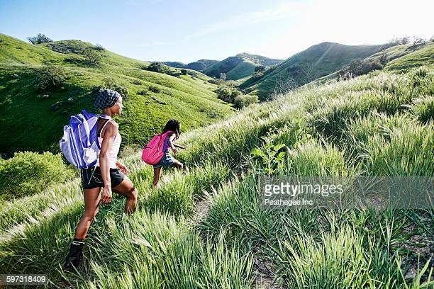 Black mother and daughter walking on rural hillside