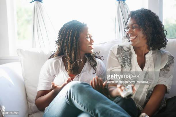 Black mother and daughter watching television together