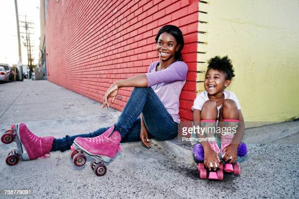 black mother and daughter wearing roller skates sitting on sidewalk - sports footwear stock pictures, royalty-free photos & images