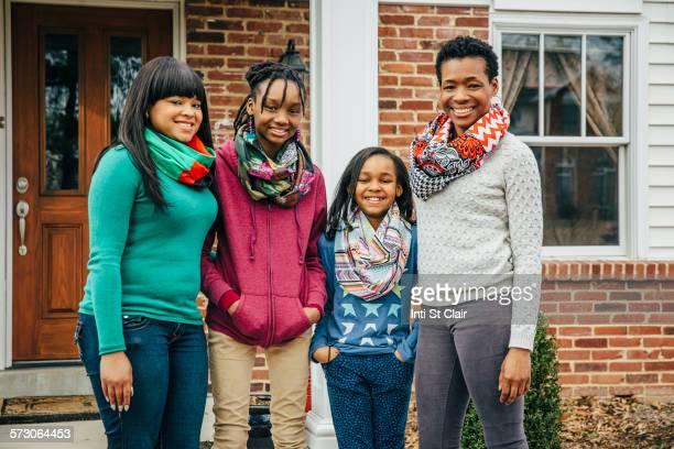 black mother and daughters smiling outside house - familie met drie kinderen stockfoto's en -beelden