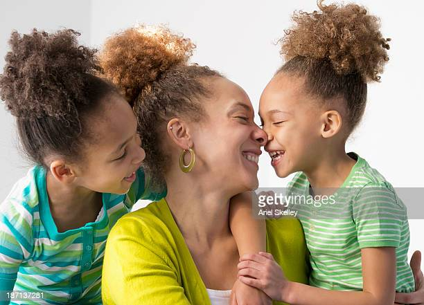 Black mother and daughters smiling together