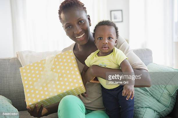 Black mother and son holding gift on sofa