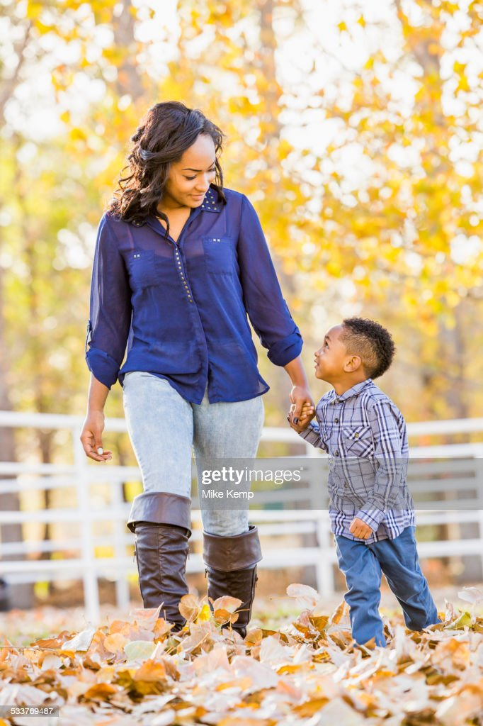 Black mother and son holding hands in autumn leaves : Foto stock
