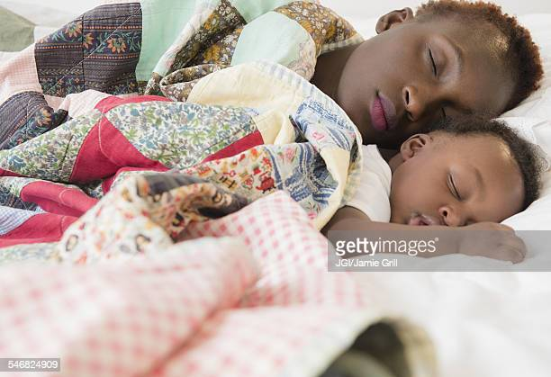 Black mother and son sleeping on bed