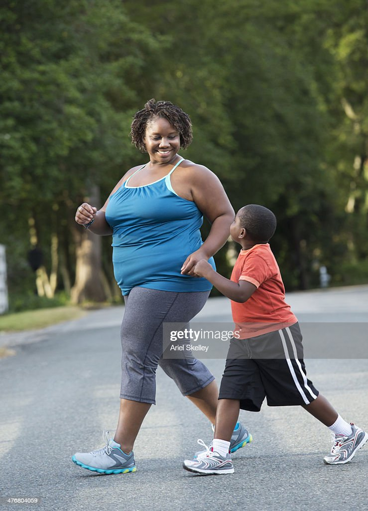 Black mother and son walking on road : Stock Photo