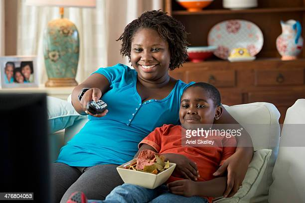 black mother and son watching television together - images of fat black women stock photos and pictures