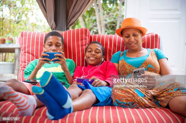 Black mother and twin sons using cell phones outdoors
