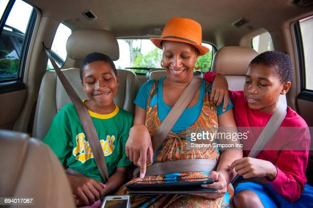 Black mother and twin sons using digital tablet in car