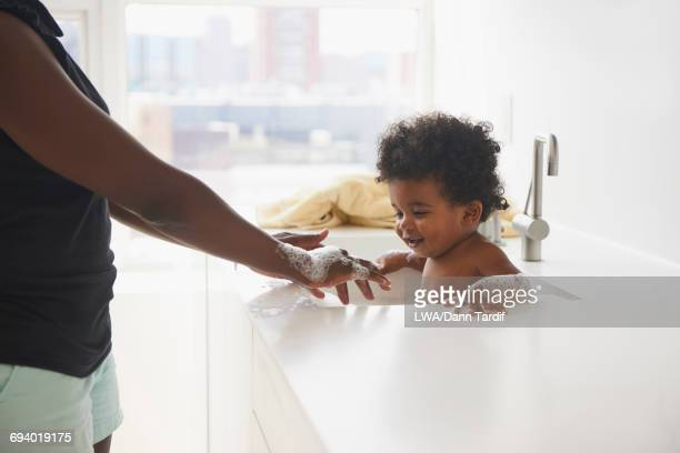 Black mother bathing baby son in sink