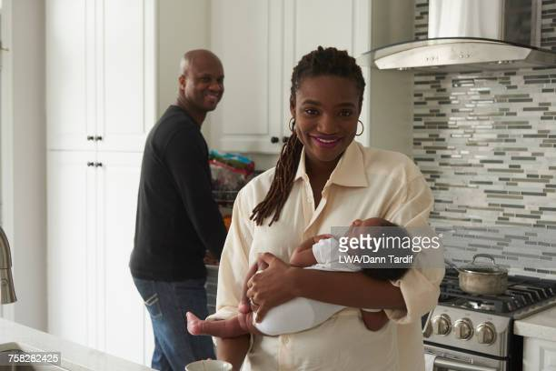 Black mother carrying sleeping baby son in domestic kitchen