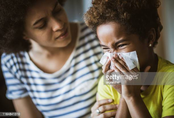 black mother consoling her daughter who is blowing a nose. - blowing nose stock pictures, royalty-free photos & images