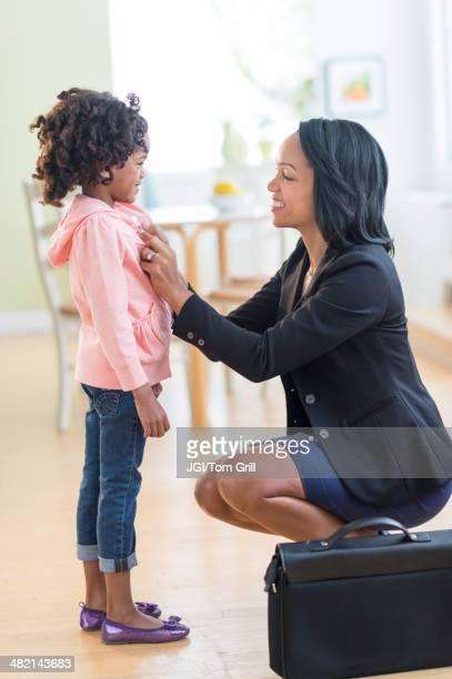 Black mother dressing daughter