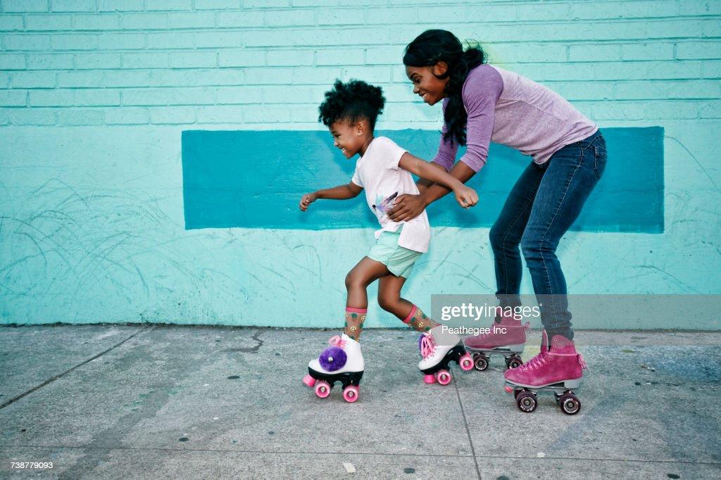 Black mother holding waist of daughter wearing roller skates : Stock-Foto