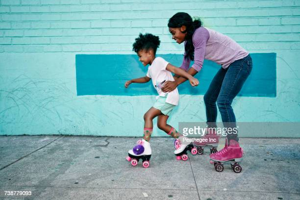 Black mother holding waist of daughter wearing roller skates