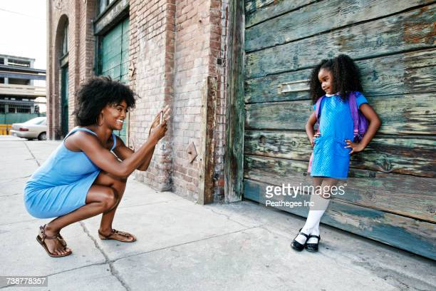 black mother photographing daughter on sidewalk with cell phone - knee length stock pictures, royalty-free photos & images