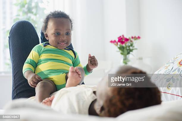 Black mother playing with baby boy on bed