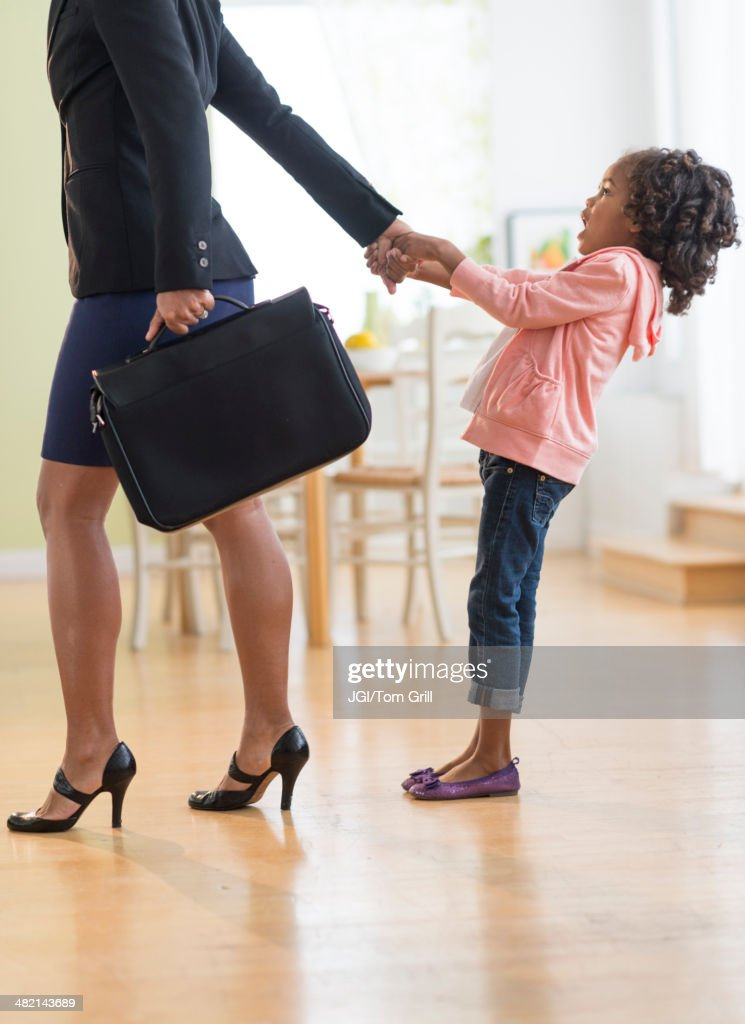 Black mother pulling anxious daughter : Stock Photo
