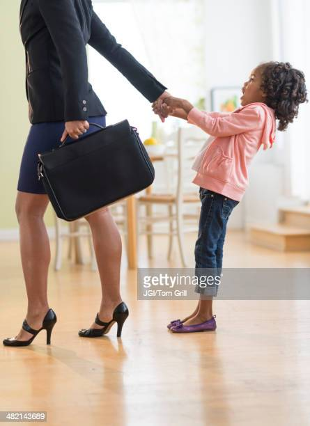 Black mother pulling anxious daughter