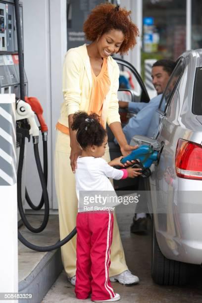Black mother teaching daughter to pump gas
