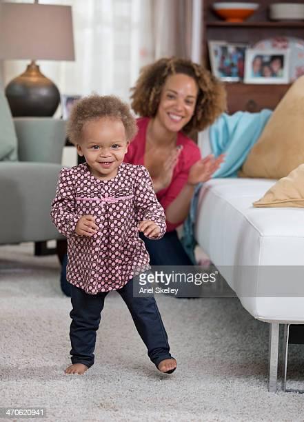 Black mother watching toddler walk