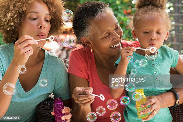 black multi-generation family blowing bubbles outdoors - afro amerikaanse etniciteit stockfoto's en -beelden